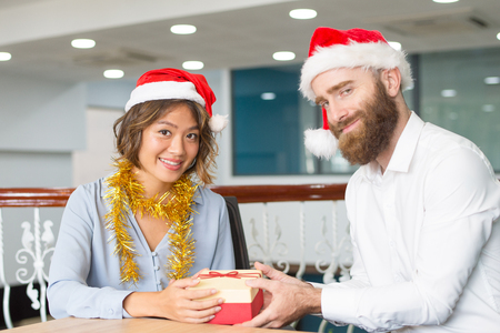 Content business colleagues in Santa hats exchanging Christmas presents. Bearded employee giving gift to smiling female colleague. Christmas presents concept