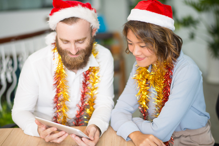 Two business colleagues having Christmas video chat with partners. Young man and woman in Santa hats smiling at tablet screen. Christmas and communication concept
