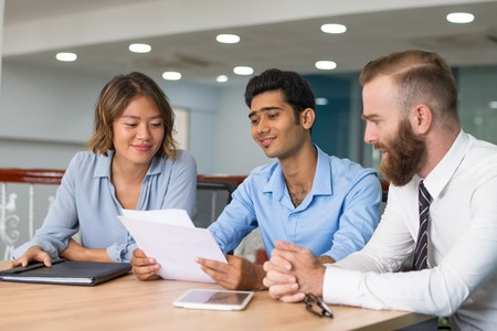 Marketing group analyzing strategy. Content young men and woman in formal shirts studying and discussing documents at meeting table. Paperwork concept
