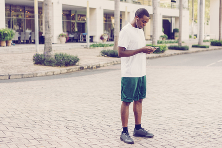 Focused black tourist getting ready for jogging and setting playlist on phone. Full length of young sporty Afro American man with smartphone and earphones. Music for run concept