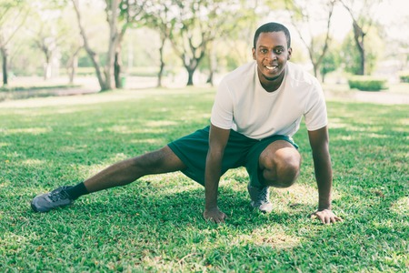 Smiling sporty black man exercising in city park or garden. Young Afro American stretching legs on grass. Fitness and street workout concept