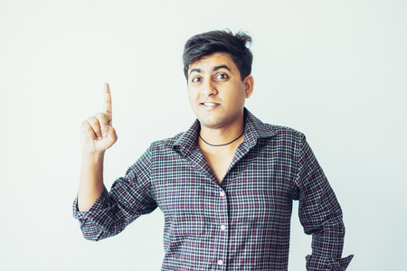 Excited young Indian guy pointing upwards and looking at camera. Idea or promotion concept. Isolated front view on grey background.