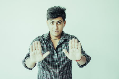 Serious young man showing open palms or stop gesture and looking at camera. Stop concept. Isolated front view on white background.