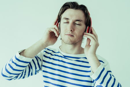 Calm relaxed man with closed eyes enjoying music. Serene handsome guy in headphones listening to favorite song. Entertainment concept