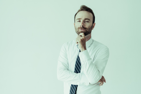 Sneaky business man touching chin, thinking and looking at camera. Sly business man concept. Isolated front view on grey background.