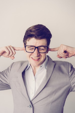 Unhappy frustrated young businessman plugging ears by fingers because of noise. Stressed employee in eyeglasses annoyed with sounds. Negative emotion concept