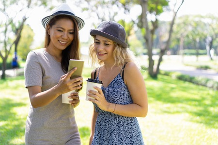 Cheerful multi-ethnic friends reading Internet news on smartphone while drinking coffee in summer park. Positive attractive young women in casual outfits using modern app on gadget. Technology concept