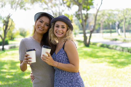 Excited beautiful lesbian couple hugging and drinking coffee in park. Cheerful young women in hats looking at camera. Walking together concept