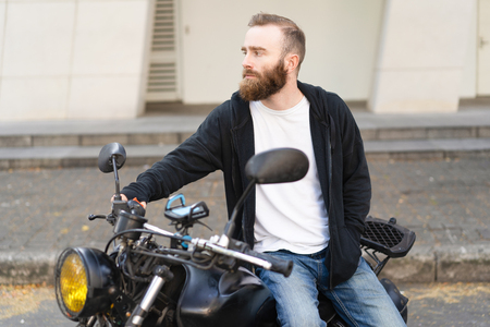Thoughtful biker lost in new city. Young hipster man sitting on motorbike and looking away. Travelling by motorbike concept Stok Fotoğraf