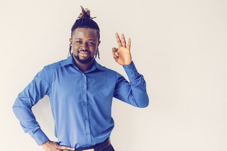 Positive confident young male manager showing ok sign as symbol of performed work. Content successful handsome black man with Afro hairstyle gesturing and looking at camera. Approved concept