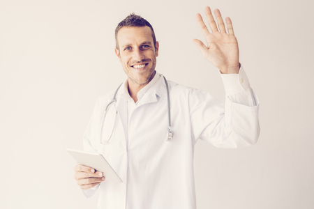 Portrait of cheerful mid adult doctor with pc tablet waving hand. Caucasian medic wearing lab coat and stethoscope greeting his clients. Healthcare concept 写真素材