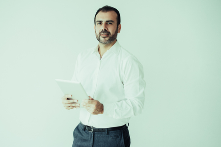 Portrait of confident mid adult manager with digital tablet. Caucasian bearded man wearing white shirt standing with touchpad. Modern businessman concept