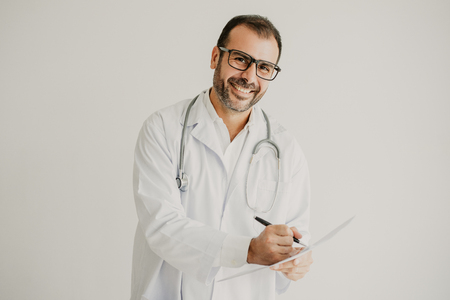 Portrait of successful general practitioner signing contract. Mid adult Caucasian doctor wearing lab coat, glasses and stethoscope making notes. Prescription or contract concept