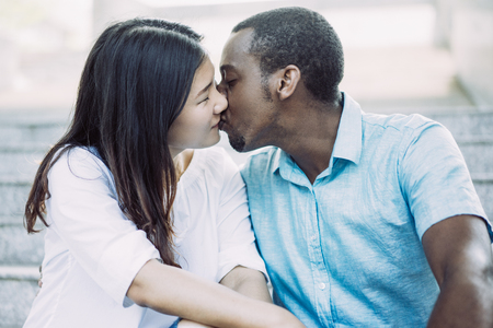 Portrait of happy young multiethnic couple kissing on stairs. Asian woman and African American man dating outdoors. Love concept