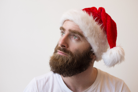 Pensive bearded man wearing Santa hat. Handsome young guy looking away. Christmas planning concept. Isolated closeup view on white background.