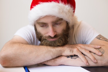 Dreamy business man wearing Santa hat and relaxing at desk. Bearded guy lying on desk with papers. Christmas and business concept. Front view.