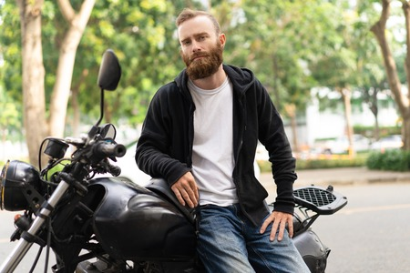 Portrait of serious young man sitting on motorcycle outdoors. Caucasian biker posing on motorbike and looking at camera. Biker man concept Stockfoto