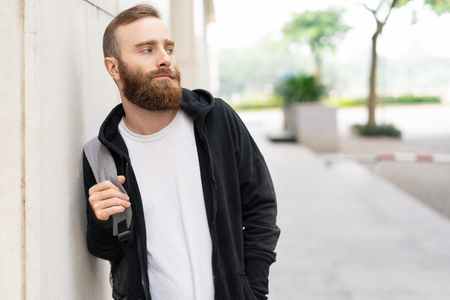Portrait of serious young bearded man with backpack outdoors. Caucasian tourist walking in city. Tourism concept