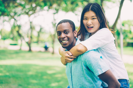 Excited young multiethnic couple enjoying piggyback ride in summer park. Jolly lovers walking together and looking at camera. Carefree date concept
