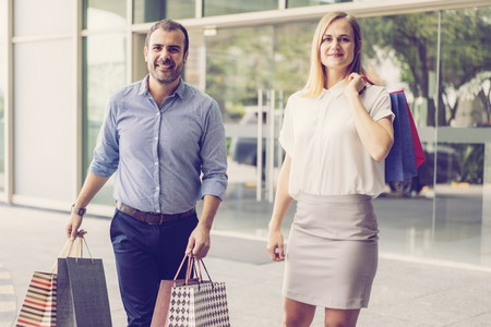 Happy middle-aged couple shopping, carrying paper bags, looking at camera and walking on city street with store glass doors in background. Shopping concept. Front view.