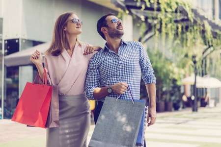Two happy consumers attracted by advertisement on outdoor digital billboard screen. Stylish couple with shopping bags standing on street and looking up. Shopping, leisure and advertising concept Stock Photo