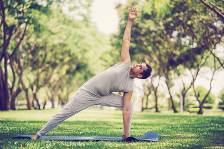 Inspired Indian man doing yoga asanas in city park. Young citizen exercising outside and standing in yoga side angle pose. Fitness outdoors and life balance concept Stock Photo