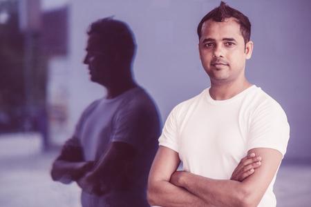 Porträt des selbstbewussten indischen Mannes im Sport-T-Shirt, das in der Glasoberfläche reflektiert wird. Hübscher Yogalehrer mit verschränkten Armen, die draußen an der Kamera aufwerfen. Menschen- und Berufskonzept Standard-Bild
