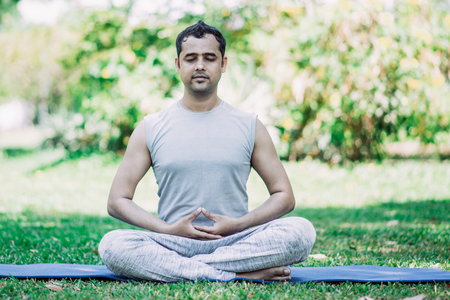 Focused young Indian man meditating in lotus pose. Calm young yogi practicing lesson outdoors in park. Yoga and fitness concept Stock Photo