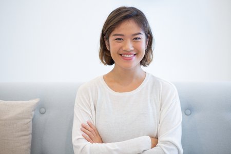 Portrait of smiling young woman looking at camera. Cheerful Asian girl sitting on coach with folded arms. Beauty concept