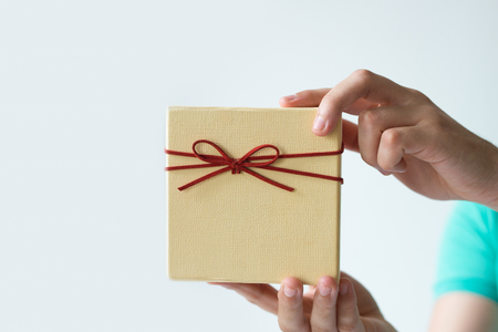 Closeup of man hands holding gift box with bow. Wrapped gift. Gift concept. Isolated cropped front view on white background.
