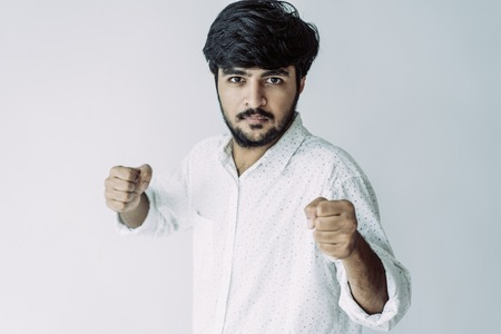 Serious brave Indian man with beard in fighting position. Confident handsome young man in casual shirt holding hands in fists and looking at camera. Battle concept Фото со стока