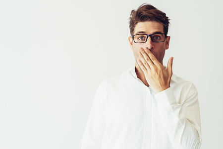 Surprised young man covering mouth with hand. Embarrassed handsome guy. Embarrassment concept. Isolated front view on white background. Archivio Fotografico