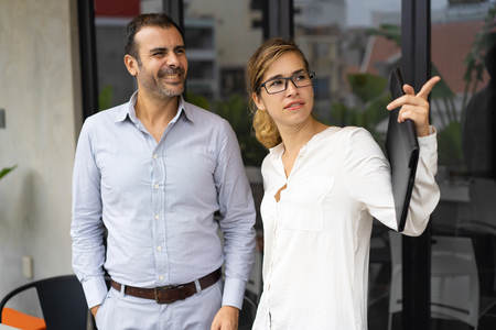 Confident businesswoman showing something to male colleague. Young Caucasian man talking to his female colleague in office. Planning concept