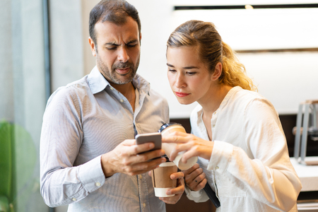 Serious male and female colleagues reading message on cellphone during coffee break. Young Caucasian businesswoman and watching data on smartphone of mid adult businessman. Mobile technology concept