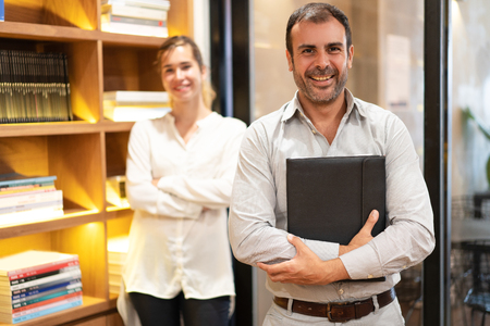 Portrait of confident mid adult executive with secretary standing behind. Caucasian bearded man holding folder, looking at camera and smiling in his office. Success concept Zdjęcie Seryjne
