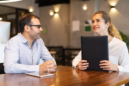 Smiling young female candidate at job interview with hr manager. Mid adult businessman wearing glasses having meeting with female client. Employment or meeting with client concept