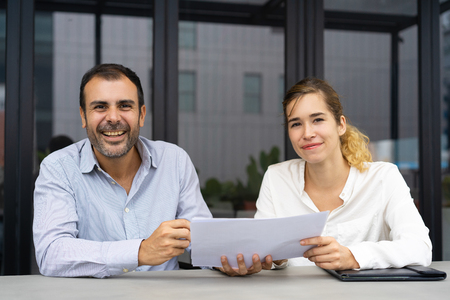 Positive confident experts analyzing reports. Male and female business colleagues holding documents and smiling at camera. Expertise concept Zdjęcie Seryjne