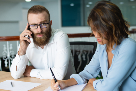 Serious frowning bearded businessman talking on phone while his assistant making notes in paper. Confused manager in glasses listening to business partner on phone. Business communication concept Zdjęcie Seryjne