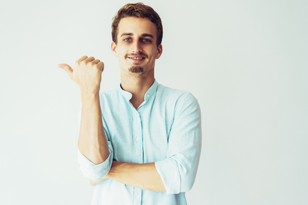 Content smiling blonde guy presenting new product. Young Caucasian man pointing thumb at copy space aside. Advertising concept