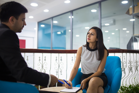 Serious young female secretary writing down notes of male leader. Caucasian businessman and businesswoman sitting on lobby and having discussion. Meeting and partnership concept