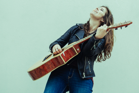 Happy inspired female guitarist performing song. Amazed young woman in leather jacket excited with playing guitar. Euphoria and street music concept Reklamní fotografie