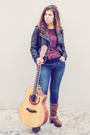 Pensive female street musician getting up for playing. Full length portrait of long haired young woman in jeans and leather jacket holding guitar and looking aside. Street music concept