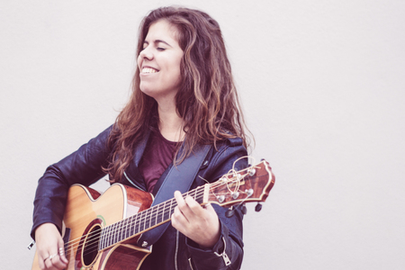 Portrait of happy female street performer. Long haired young woman in leather jacket enjoying playing guitar. Street music concept