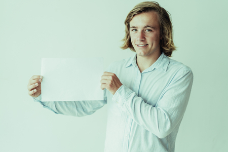 Cheerful blonde guy presenting new product. Long haired young man in white shirt holding empty sheet of paper. Presentation or promotion concept
