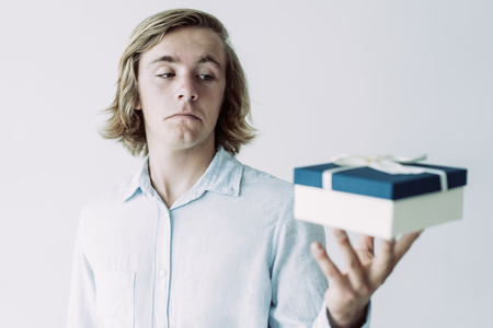 Confused handsome guy disappointed with gift box size. Long haired young Caucasian man looking at present doubtfully. Holiday or presenting concept