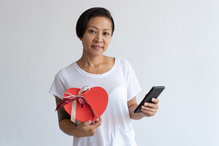 Content Asian woman holding heart shaped gift box and smartphone. Lady browsing on digital device. Valentines Day and communication concept. Isolated front view on white background. Imagens