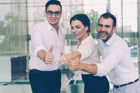 Happy business team showing thumbs-up gesture. Joyful coworkers showing motivating gesture. Support concept