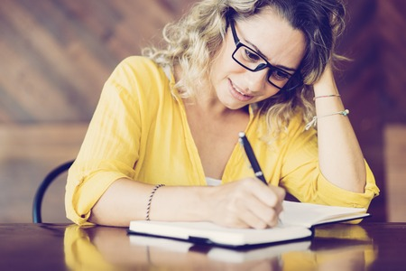 Hectic young woman in glasses writing agenda for meeting. Nervous female student doing homework at cafe table. Deadline concept