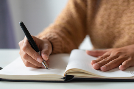 Close-up van zakenvrouw die aantekeningen maakt in persoonlijke organizer. Onherkenbare dame die in dagboek schrijft. Tijdsconcept plannen