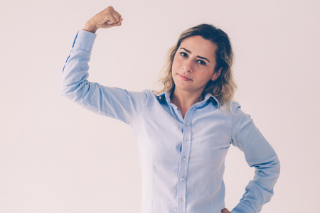 Portrait of confident young female leader showing muscle. Caucasian businesswoman making strength gesture. Leadership and strength concept